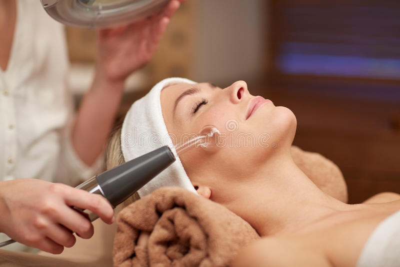 Ciérrese para arriba de la mujer joven que tiene masaje de cara en balneario foto de archivo
