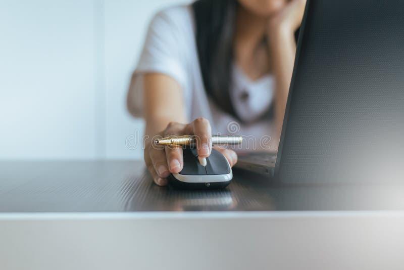 Ciérrese para arriba de la mujer de la mano serching y haga clic el ratón usando el ordenador portátil fotos de archivo