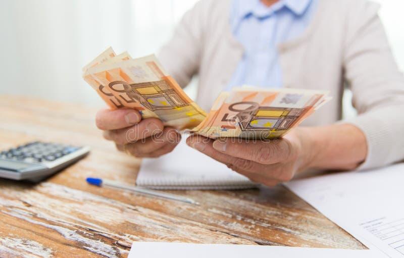 Ciérrese para arriba de la mujer mayor que cuenta el dinero en casa foto de archivo libre de regalías
