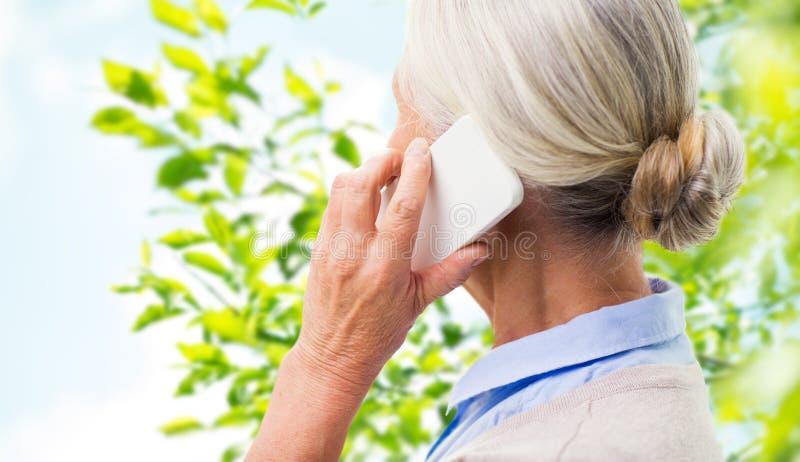 Ciérrese para arriba de la mujer mayor que invita a smartphone imagenes de archivo