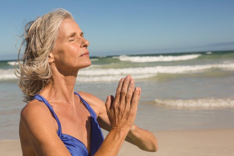 Ciérrese para arriba de la mujer mayor que medita en la playa fotos de archivo libres de regalías