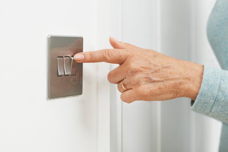 Ciérrese para arriba de la mujer que apaga el interruptor de la luz foto de archivo