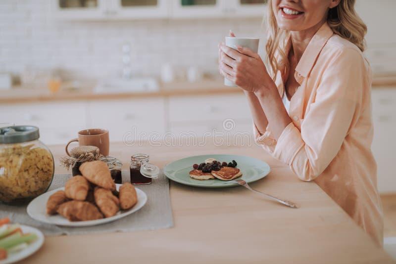 Ci?rrese para arriba de la mujer que come las crepes y que bebe t? foto de archivo libre de regalías