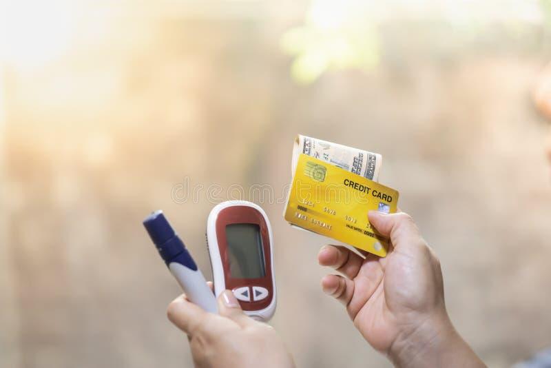 Ciérrese para arriba de la mujer que lleva a cabo el metro de la glucosa, la lanceta, la tarjeta de crédito y dólares americanos  fotos de archivo