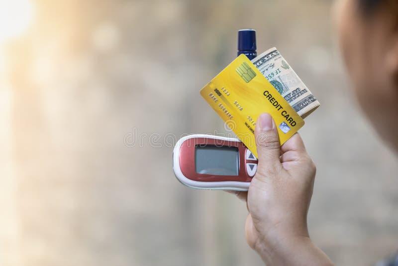 Ciérrese para arriba de la mujer que lleva a cabo el metro de la glucosa, la lanceta, la tarjeta de crédito y dólares americanos  foto de archivo