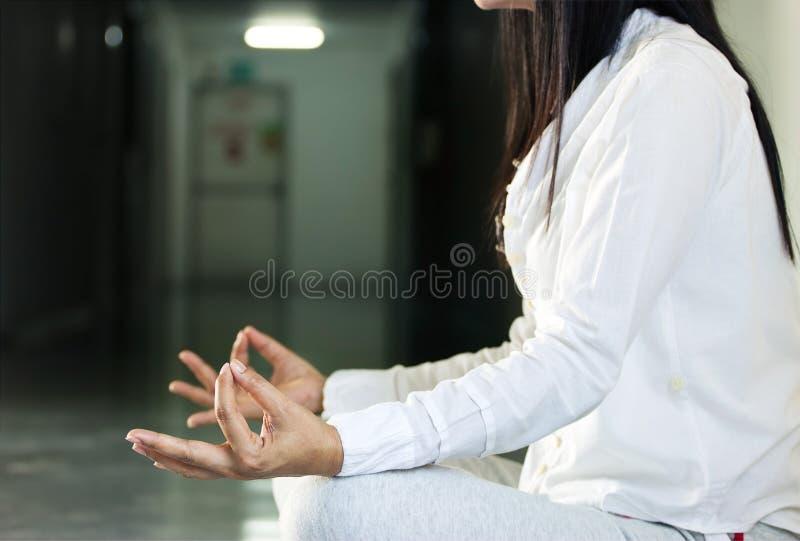 Ciérrese para arriba de la mujer que medita sentarse en pasillo fotos de archivo