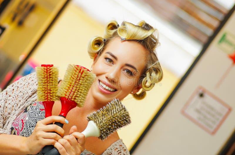 Ciérrese para arriba de la mujer que sostiene en sus manos muchos cepillos de la ronda, en un salón de pelo en fondo ablurred foto de archivo libre de regalías
