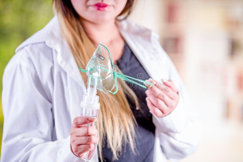 Ciérrese para arriba de la mujer que sostiene en sus manos un nebulizador para el asma y las enfermedades respiratorias en casa imagenes de archivo