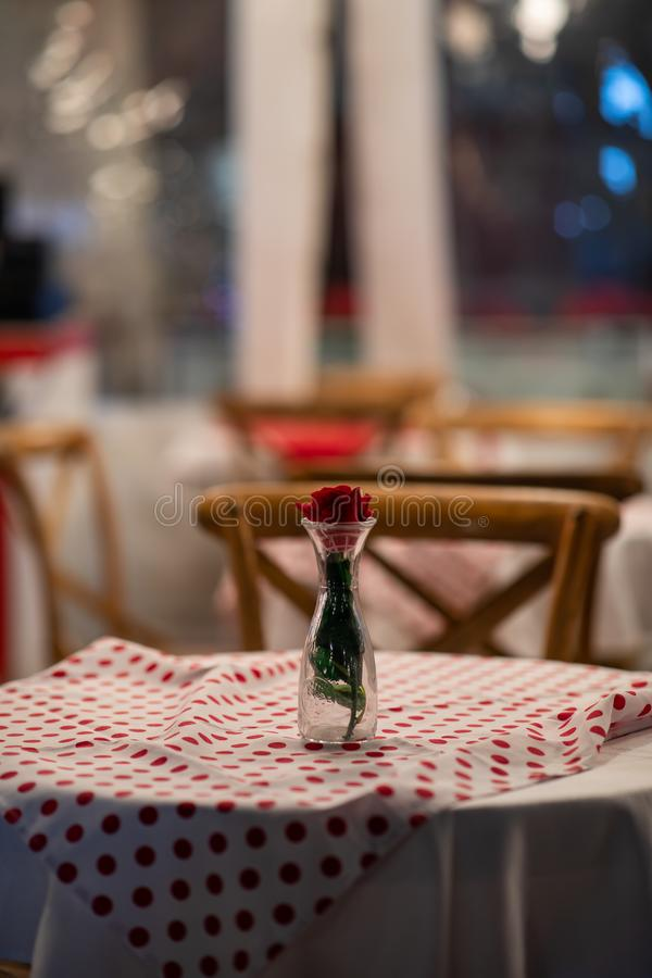 Ciérrese para arriba de la pieza central de una tabla española del restaurante con el mantel a cuadros rojo y las sillas de mader imágenes de archivo libres de regalías
