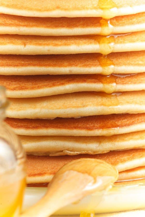 Ciérrese para arriba de la pila de crepe con la miel de colada, la cuchara de madera y el tarro de miel fotos de archivo libres de regalías