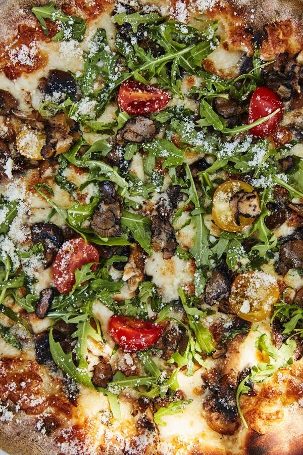Ciérrese para arriba de la pizza con la trufa, el cohete, los tomates de cereza y los quesos italianos fotografía de archivo