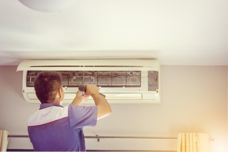 Ciérrese para arriba de la reparación del aire acondicionado, reparador en el fixi del piso fotografía de archivo libre de regalías