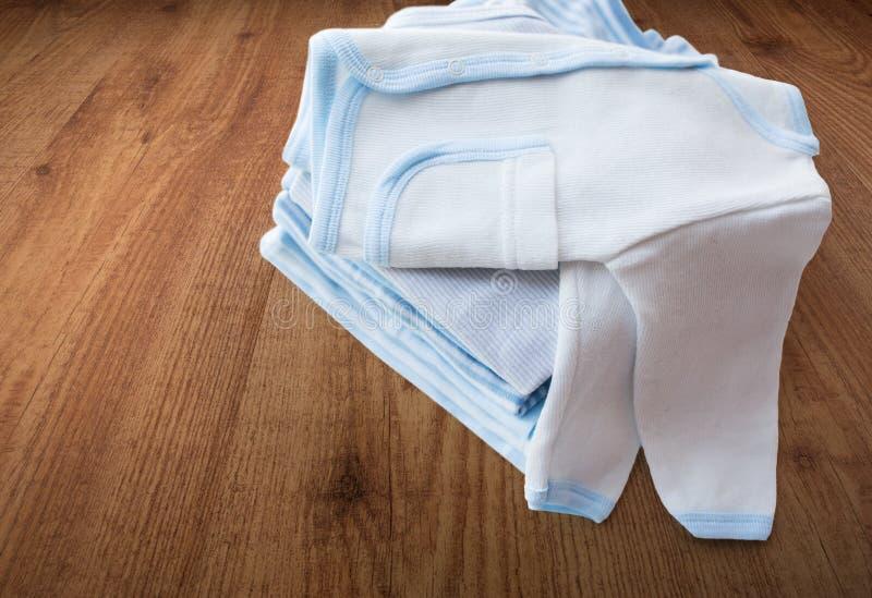 Ciérrese para arriba de la ropa de los bebés para recién nacido en la tabla fotografía de archivo libre de regalías