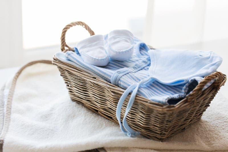 Ciérrese para arriba de la ropa del bebé para el muchacho recién nacido en cesta foto de archivo