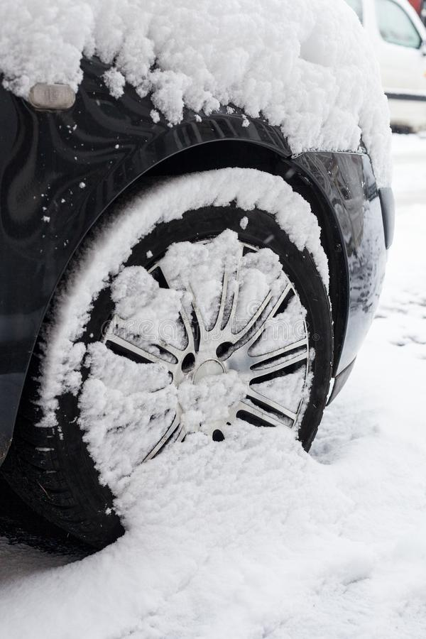 Ciérrese para arriba de la rueda de coche cubierta con nieve en día de invierno frío de la calle fotos de archivo