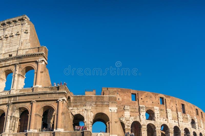 Ciérrese para arriba de la señal famosa de Roman Coliseum con los turistas imágenes de archivo libres de regalías
