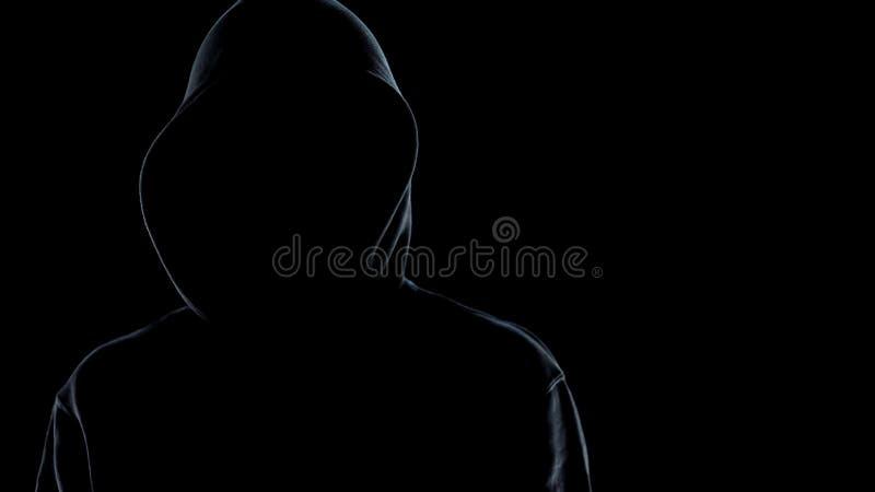 Ciérrese para arriba de la situación masculina anónima de la silueta contra fondo negro, criminal fotografía de archivo