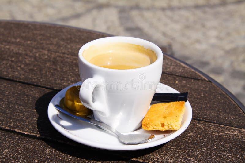 Ciérrese para arriba de la taza blanca aislada del café express con el platillo, la cuchara y la galleta dulce imágenes de archivo libres de regalías
