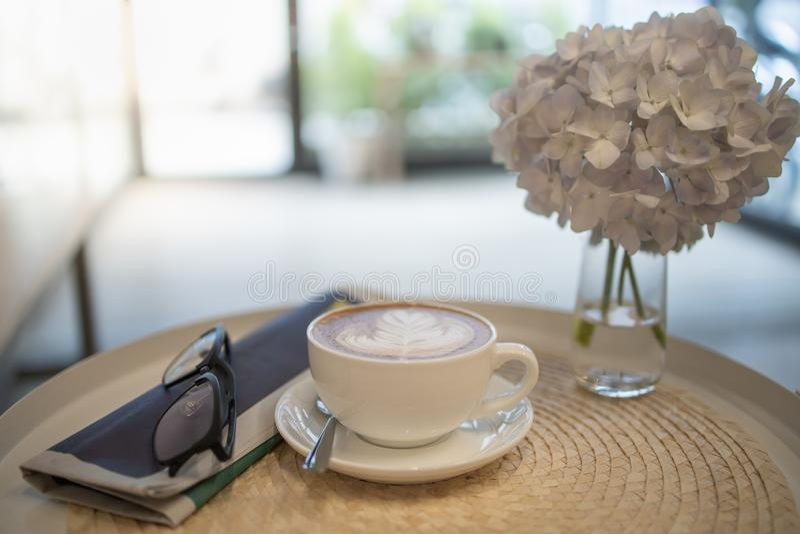 Ciérrese para arriba de la taza caliente de latte del café con arte de la forma del corazón de la leche con el periódico y los vi fotos de archivo