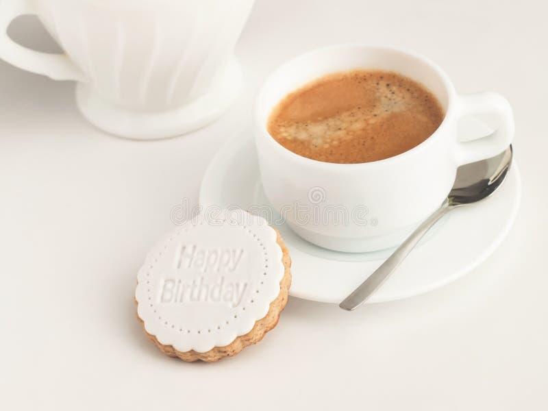 Ciérrese para arriba de la taza de café y de la galleta cubierta pasta de azúcar Decoración del feliz cumpleaños en el top imágenes de archivo libres de regalías