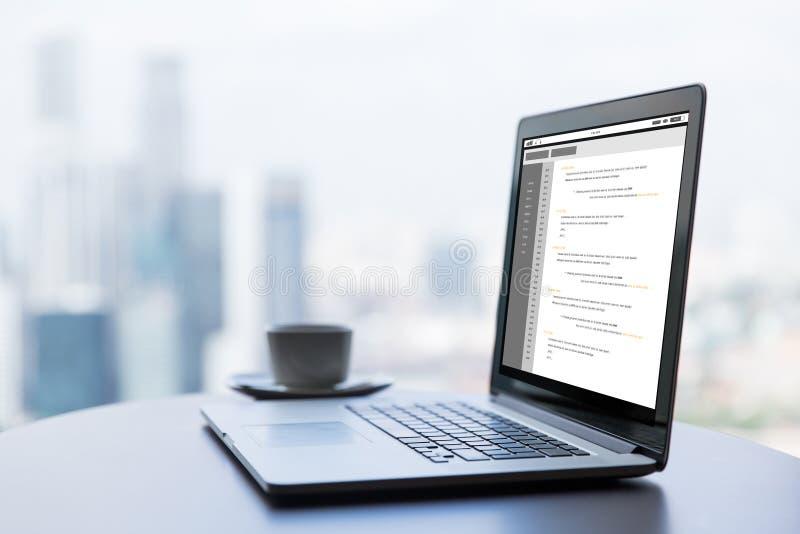 Ciérrese para arriba de la taza del ordenador portátil y de café en la tabla de la oficina imagen de archivo