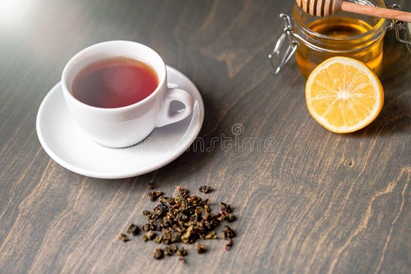 Ciérrese para arriba de la taza de té con el limón, el jengibre y la miel en la tabla rústica de madera fotografía de archivo