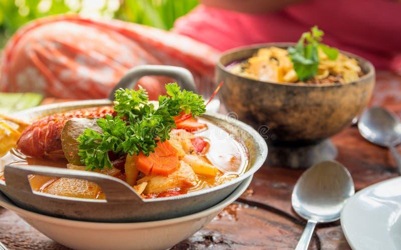 Ciérrese para arriba de langosta del estilo y del cuenco de sopa de verduras asiáticos foto de archivo