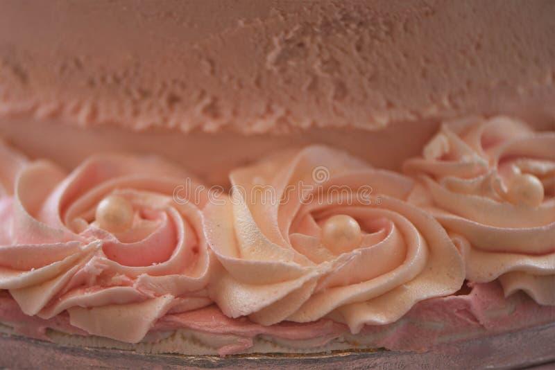 Ciérrese para arriba de las flores del remolino y de las decoraciones rosadas heladas de la perla en un pastel de bodas imagenes de archivo