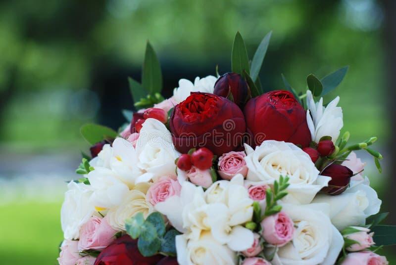 Ciérrese para arriba de las flores rosadas y blancas de Peonny que se casan y de las rosas con brunch del eucalipto imagen de archivo