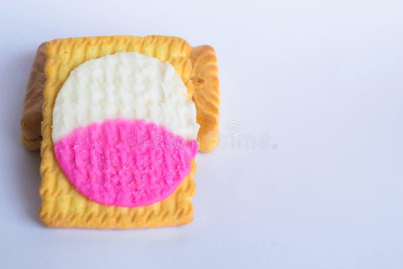 Ciérrese para arriba de las galletas cuadradas de la forma llenadas de la crema blanca y rosada aislada en un fondo blanco fotografía de archivo