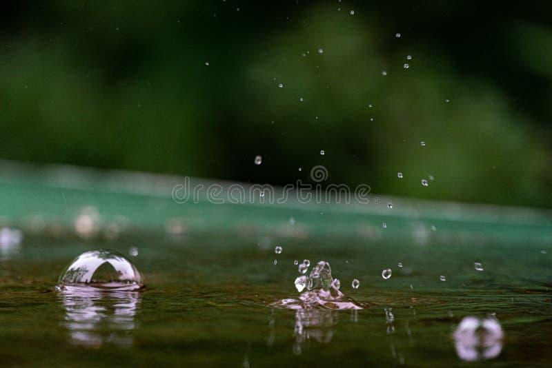 Ciérrese para arriba de las gotas de agua que salpican en una tabla verde imágenes de archivo libres de regalías