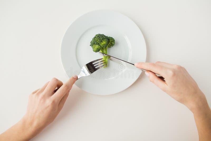 Ciérrese para arriba de las manos de la mujer que comen el bróculi imagenes de archivo