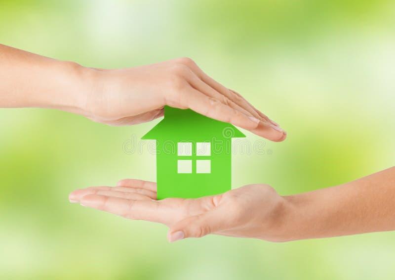 Ciérrese para arriba de las manos de la mujer que sostienen la casa verde imagen de archivo