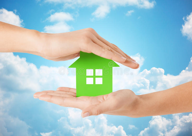 Ciérrese para arriba de las manos de la mujer que sostienen la casa verde fotos de archivo libres de regalías