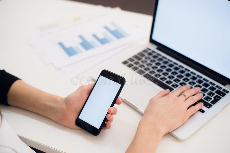 Ciérrese para arriba de las manos de la mujer usando el teléfono móvil y el ordenador portátil con la pantalla en blanco del espa fotografía de archivo libre de regalías
