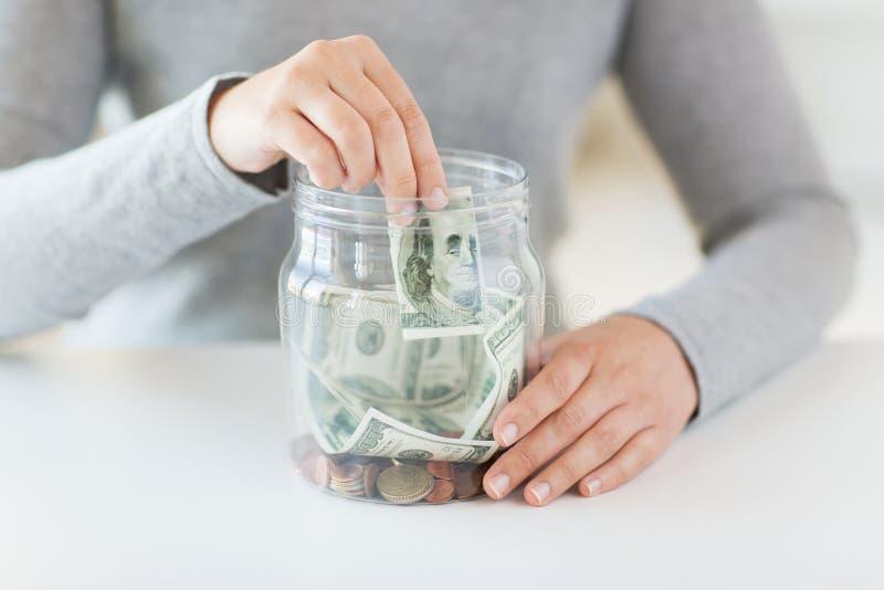 Ciérrese para arriba de las manos de la mujer y del dinero del dólar en tarro fotos de archivo libres de regalías
