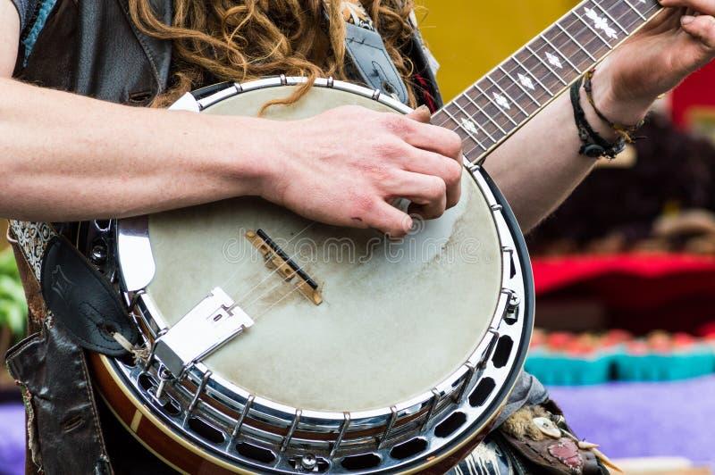 Ciérrese para arriba de las manos de los jugadores de un banjo que tocan el banjo en un mercado de los granjeros imagenes de archivo