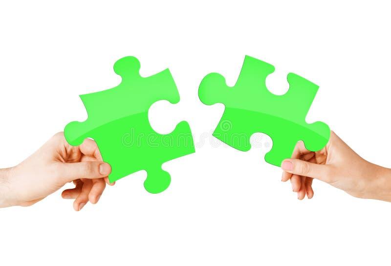 Ciérrese para arriba de las manos de los pares con los pedazos verdes del rompecabezas foto de archivo
