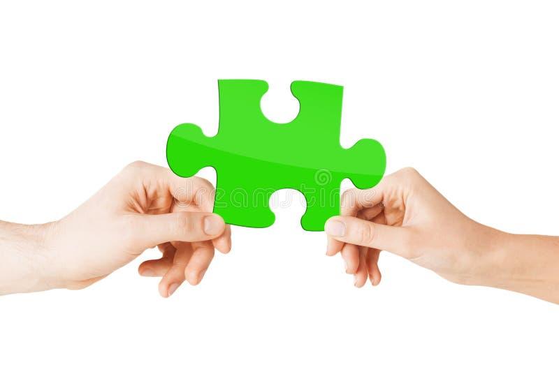 Ciérrese para arriba de las manos de los pares con rompecabezas verde foto de archivo libre de regalías