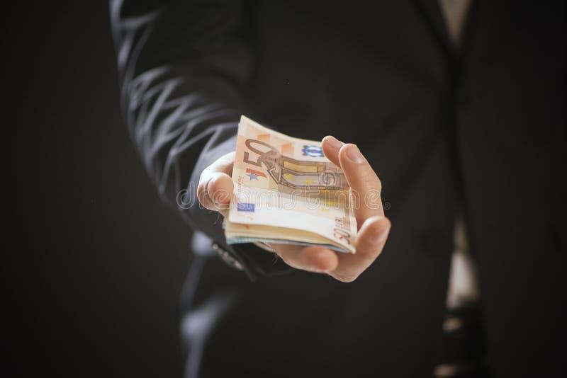 Ciérrese para arriba de las manos de un hombre de negocios que ofrecen el dinero imágenes de archivo libres de regalías