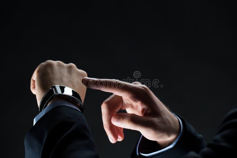 Ciérrese para arriba de las manos del hombre de negocios con el reloj elegante foto de archivo