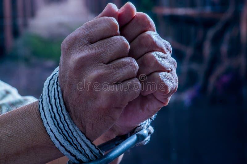 Ciérrese para arriba de las manos del hombre envueltas con la cuerda alrededor de las muñecas en cautiverio, víctima abusada, esc fotos de archivo libres de regalías