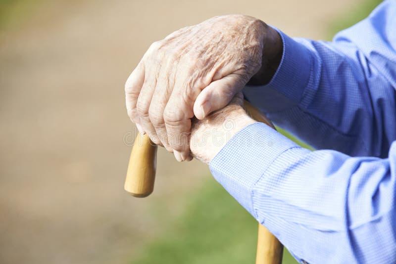 Ciérrese para arriba de las manos del hombre mayor que descansan sobre el bastón fotos de archivo