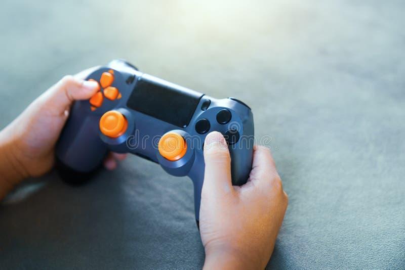 Ciérrese para arriba de las manos del niño que juegan al videojuego, competencia del videojuego Concepto del juego fotografía de archivo libre de regalías