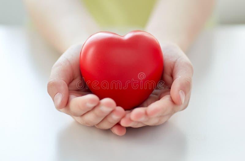 Ciérrese para arriba de las manos del niño que llevan a cabo el corazón rojo foto de archivo libre de regalías