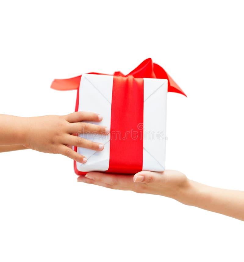Ciérrese para arriba de las manos del niño y de la madre con la caja de regalo fotos de archivo