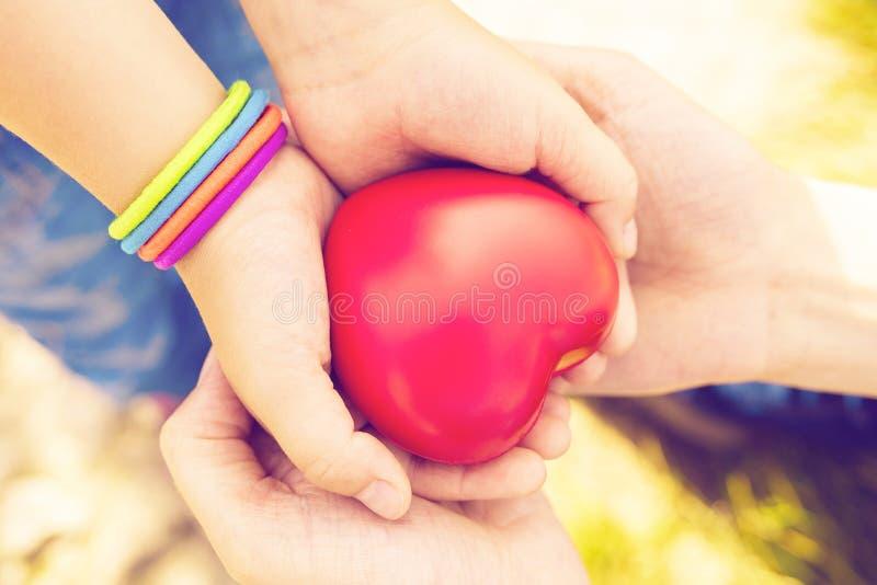 Ciérrese para arriba de las manos del niño y de la madre con el corazón imagen de archivo