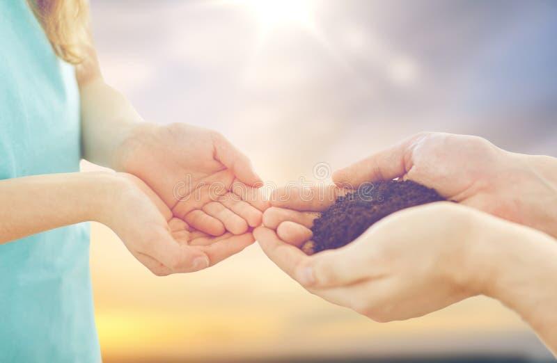 Ciérrese para arriba de las manos del padre y de la hija que sostienen el suelo imágenes de archivo libres de regalías
