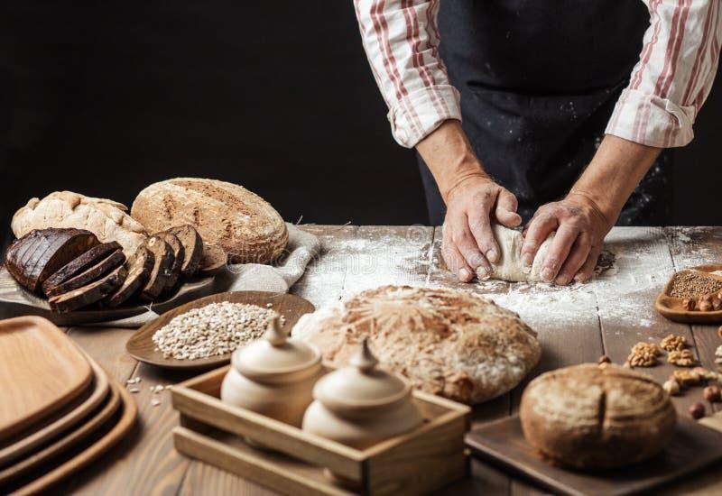 Ciérrese para arriba de las manos del panadero que amasan la pasta y que hacen el pan con un rodillo fotografía de archivo libre de regalías