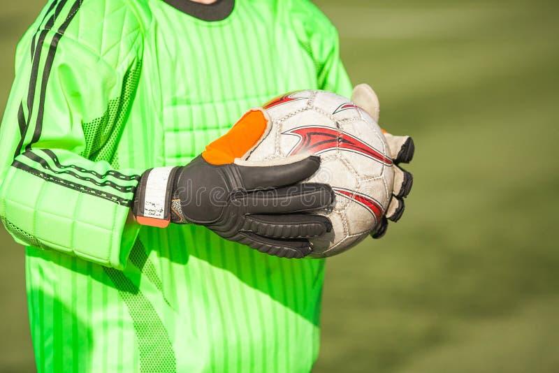 Ciérrese para arriba de las manos del portero que lleva a cabo un soccerball foto de archivo